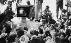 Students in a village school view a film-strip presentation on a sunlight-powered slide projector.