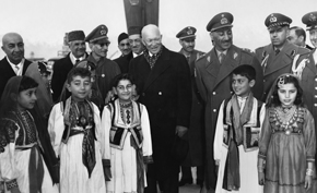 President Eisenhower is welcomed at the airport by King Zahir Shah, Afghan government officials, and children.