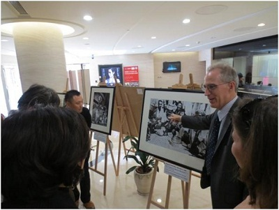 Meridian's Senior Vice President for the Arts, Dr. Curtis Sandberg explains the photographs to journalists at the Jam Session Exhibition in Shanghai