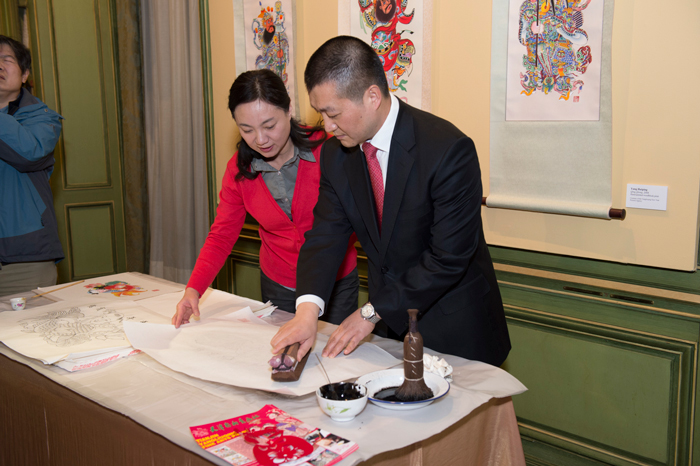 The Chinese Deputy Chief of Mission, Minister Lu Kang, and artist, Yang Huiping, demonstrate the process woodblock print making at the Chinese Lunar New Year celebration.