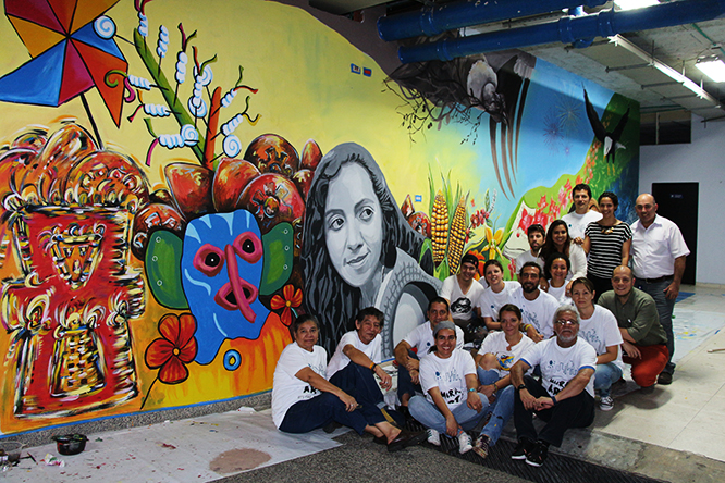 Artists pose with their mural led by American artist Augustina Droze in Cali, Colombia.